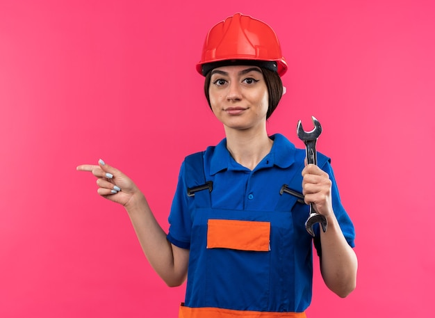 Pleased looking at camera young builder woman in uniform holding open-end wrench points at side