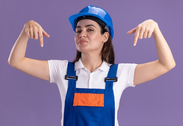 Pleased looking at camera young builder woman in uniform points at down isolated on purple wall