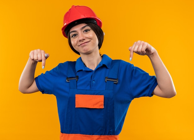 Pleased looking at camera young builder woman in uniform points at down