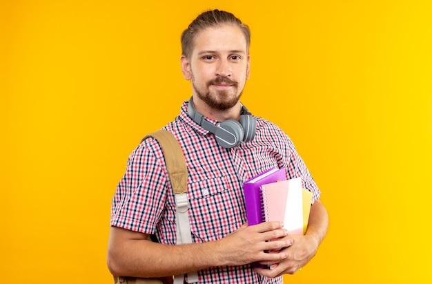 Felice guardando fotocamera giovane studente che indossa uno zaino con in mano un libro