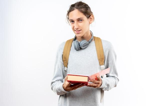 本を持っている首にヘッドフォン付きのバックパックを身に着けているカメラの若い男の学生を見て喜んで