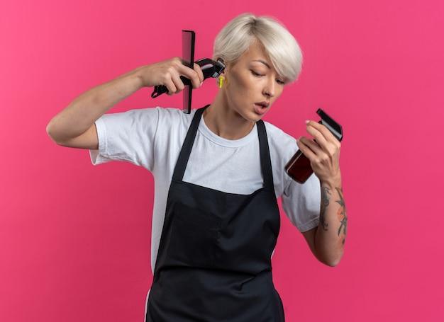 Lieto di guardare in basso la giovane bella barbiere femminile in uniforme che tiene gli strumenti del barbiere isolati sulla parete rosa