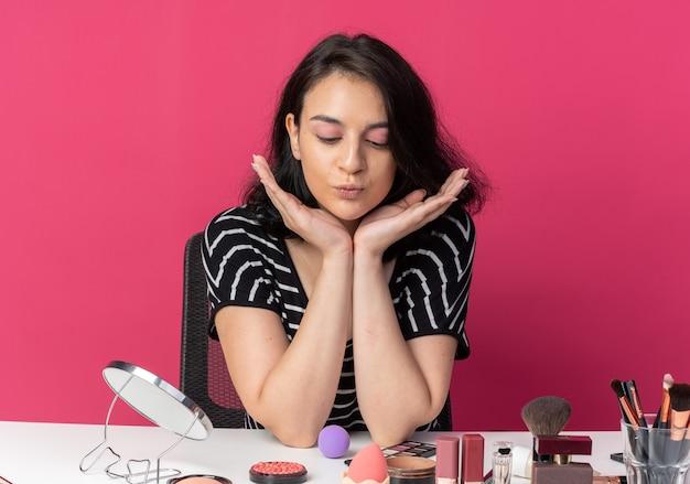 젊은 아름 다운 소녀를 내려다보고 기쁘게 생각 분홍색 벽에 고립 된 얼굴에 손을 잡고 메이크업 도구와 테이블에 앉아