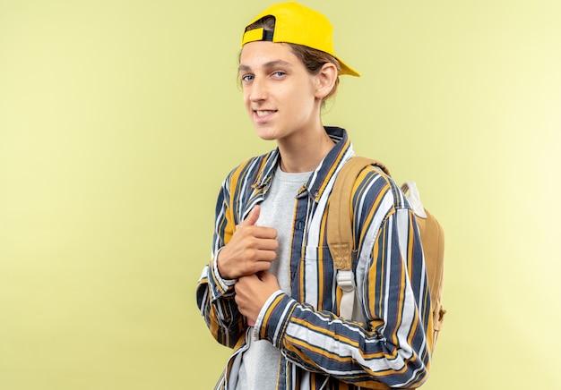 올리브 녹색 벽에 모자가 달린 배낭을 메고 앞을 바라보는 젊은 남자 학생을 기쁘게 생각합니다.