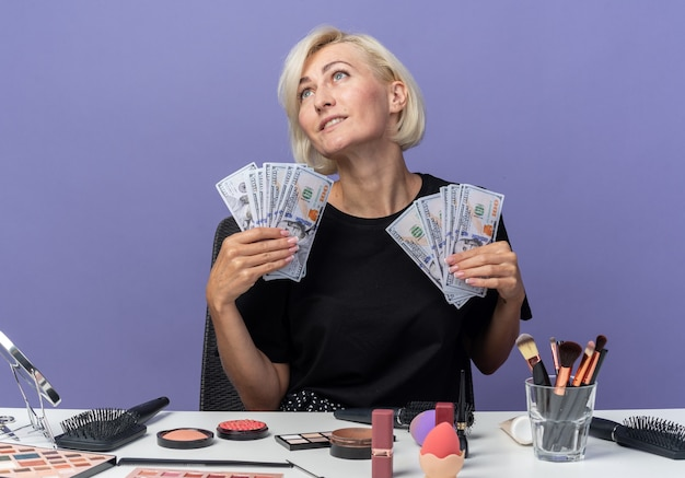 Pleased looking at side tilting head young beautiful girl sits at table with makeup tools holding cash isolated on blue wall