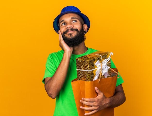 Felice guardando lato giovane ragazzo afro-americano che indossa un cappello da festa che tiene in mano una borsa regalo guancia coperta con la mano isolata sul muro arancione