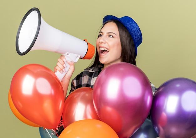 풍선 뒤에 서 있는 파란색 모자를 쓰고 있는 아름다운 소녀가 확성기로 말합니다.