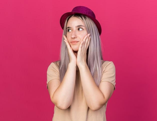 パーティーハットを身に着けている若い美しい女の子が手で頬を覆って喜んでいる