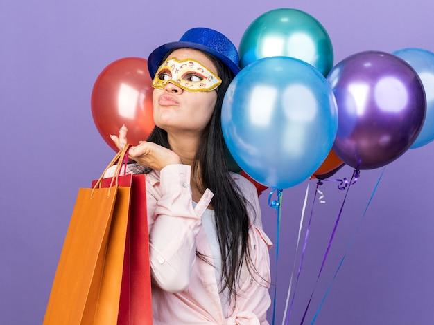 Piacere di guardare la giovane bella ragazza che indossa un cappello da festa e una maschera per gli occhi in maschera che tiene palloncini con un sacchetto regalo