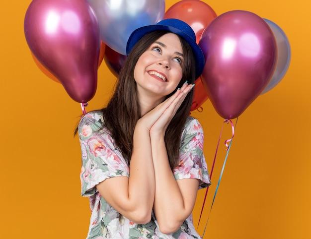オレンジ色の壁に分離された前の風船に立っているパーティーハットを身に着けている側面の若い美しい女性を喜んで見てください