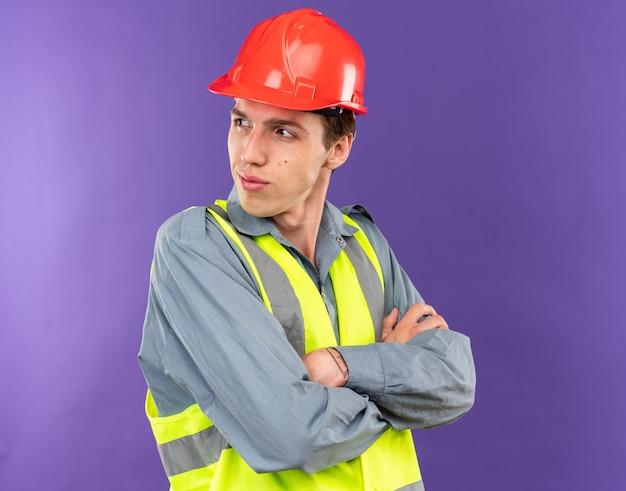 Felice guardando lato giovane costruttore uomo in uniforme attraversando le mani isolate sulla parete blu