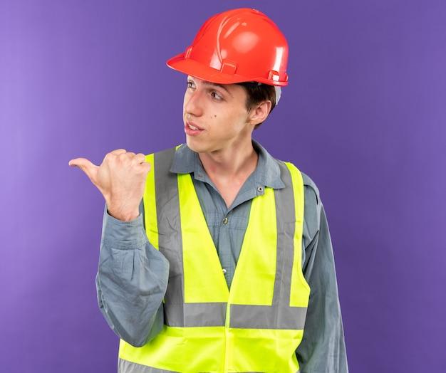 Il giovane costruttore di lato dall'aspetto contento in uniforme punta a lato
