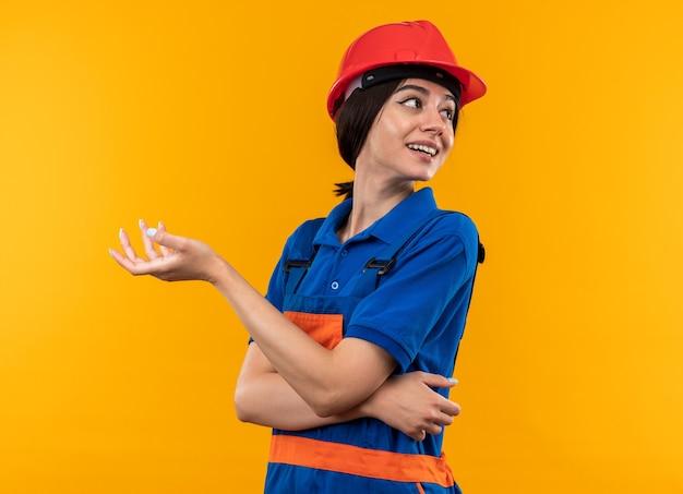 Lieto di guardare la giovane donna del costruttore in uniforme isolata sul muro giallo