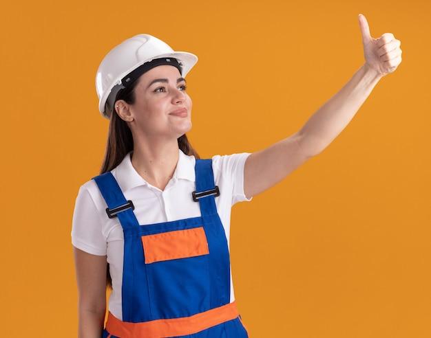Lieto di guardare di lato la giovane donna del costruttore in uniforme che mostra il pollice in alto isolato sul muro arancione