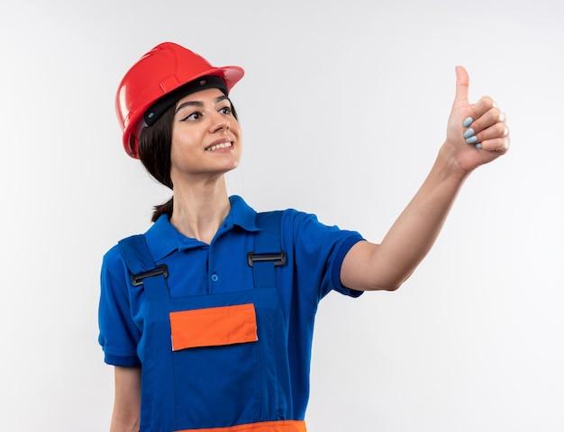 Lieto di guardare di lato la giovane donna del costruttore in uniforme che mostra il pollice in su