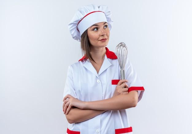 白い背景で隔離の泡立て器交差する手を保持しているシェフの制服を着て喜んでいる側の若い女性料理人