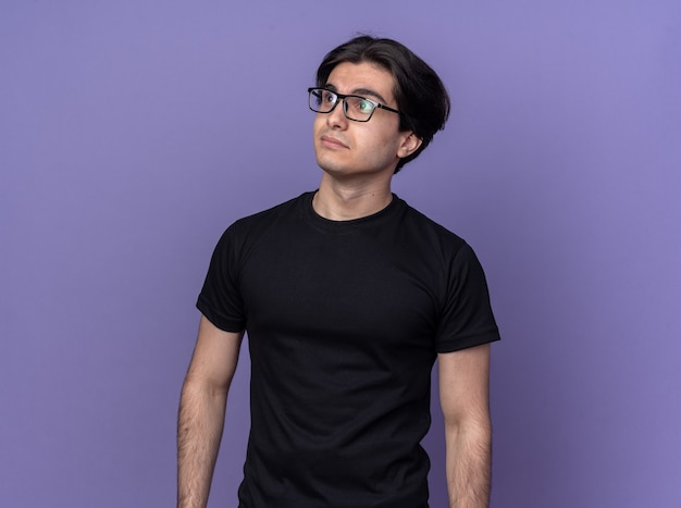 Pleased looking at side young handsome guy wearing black t-shirt and glasses isolated on purple wall