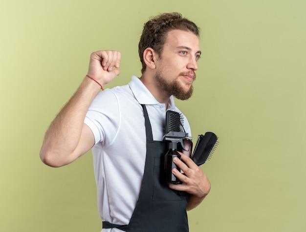 Piacere guardando lato giovane maschio barbiere indossando uniformi azienda barbiere strumenti isolati su verde oliva wall