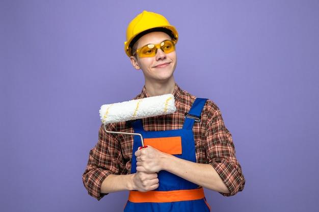 Lieto guardando lato giovane costruttore maschio indossando uniformi e occhiali tenendo la spazzola a rullo
