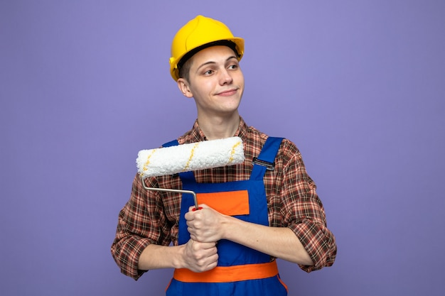 Soddisfazione del giovane costruttore maschio che indossa l'uniforme tenendo la spazzola a rullo