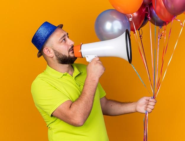 풍선을 들고 파티 모자를 쓰고 기쁘게 찾고 측면 젊은 남자는 확성기에 말한다