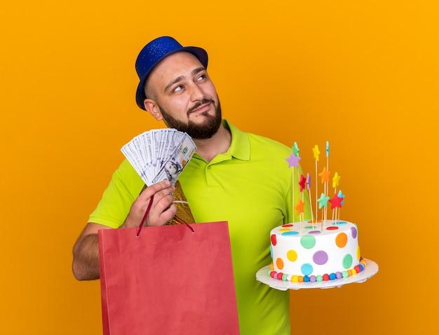Довольно выглядящий молодой человек в шляпе для вечеринки, держащий подарочный пакет с тортом и наличными, изолированный на оранжевой стене