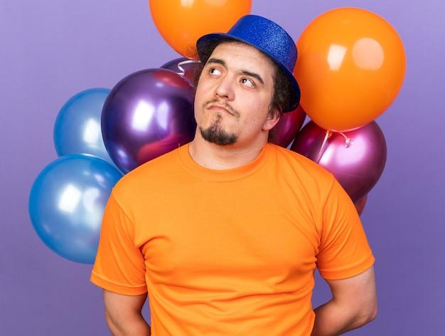 Felice guardando lato giovane che indossa cappello da festa in piedi di fronte a palloncini isolati su parete viola