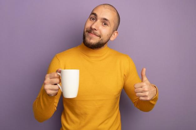 お茶のカップを保持し、紫色に分離された親指を見せてまっすぐ前を見て喜んで若いハンサムな男