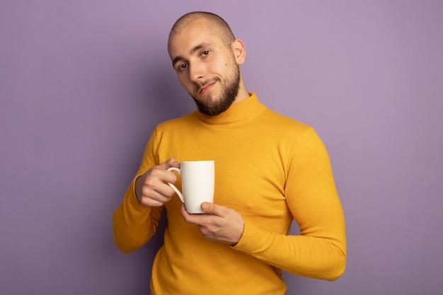 紫に分離されたお茶のカップを保持している若いハンサムな男をまっすぐに見て喜んで