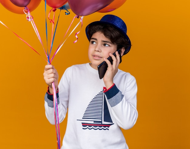 Pleased looking up little boy wearing blue party hat holding balloons and speaks on phone