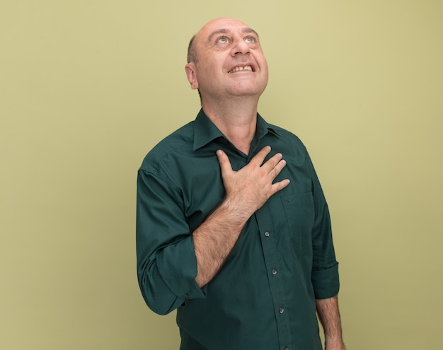 オリーブグリーンの壁に隔離された心に手を置いて緑のtシャツを着ている中年男性を見て喜んで