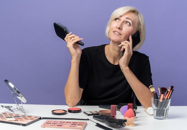 青い壁に分離された櫛を保持している電話で話す化粧ツールでテーブルに座っている若い美しい少女を見て喜んで