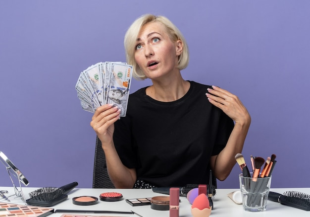 Pleased looking up young beautiful girl sits at table with makeup tools holding cash isolated on blue wall