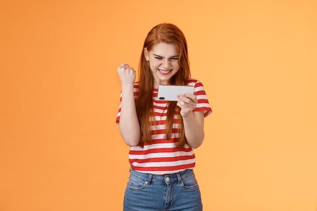 Довольная счастливая рыжая девушка-геймер рыжая накачивает кулаком довольна: да, взволнованный взгляд ...