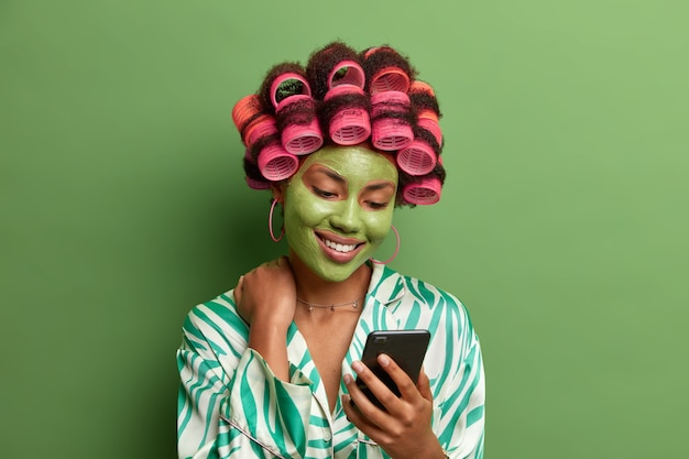 Довольная великолепная дама сосредоточена на дисплее смартфона, позитивно улыбается, когда читает сообщение, одета в повседневную одежду, носит косметическую маску, заботится о коже, бигуди для волос для идеальной прически