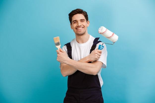 Довольный мужчина-строитель позирует с валиком и кистью над синей стеной