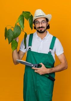 ガーデニング帽子をかぶった光学メガネで喜んでいる男性の庭師は、植物とクリッパーを保持します