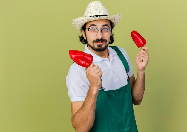 ガーデニング帽子をかぶった光学メガネで喜んでいる男性の庭師は、両手に赤唐辛子を持っています