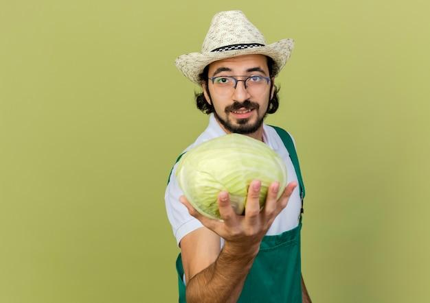 Il giardiniere maschio soddisfatto in vetri ottici che indossa il cappello di giardinaggio tiene alla ricerca del cavolo