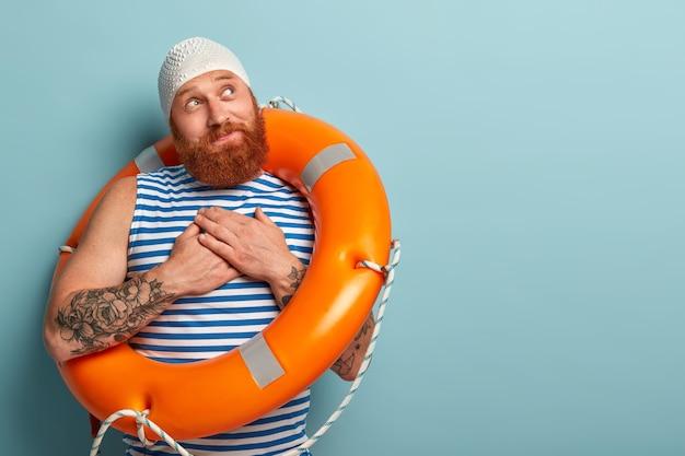 기뻐하는 남자 수영 선수는 감사의 몸짓을하고, 구명 조끼에게 감사를 느낀다. 또는 전문적인 수업에 대해 수영 강사에게 감사하며 안전하게 지낸다.