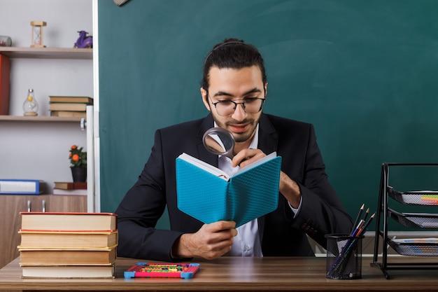 Insegnante maschio soddisfatto che indossa occhiali che tiene e legge un libro con lente di ingrandimento seduto al tavolo con strumenti scolastici in classe