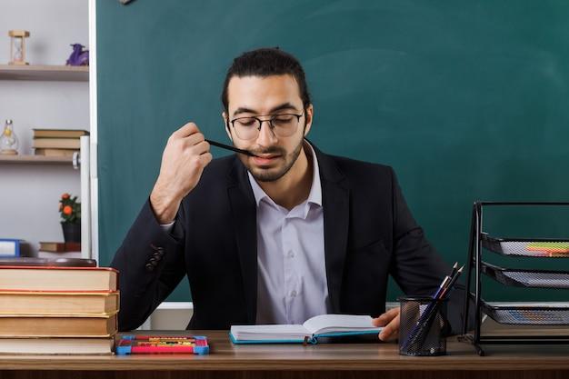 Insegnante maschio soddisfatto che indossa occhiali libro di lettura mettendo la matita in bocca seduto a tavola con gli strumenti della scuola in aula