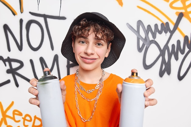 Pleased man being graffiti artist holds aerosol color cans wears hat and orange t shirt with chains around neck poses against graffiti wall