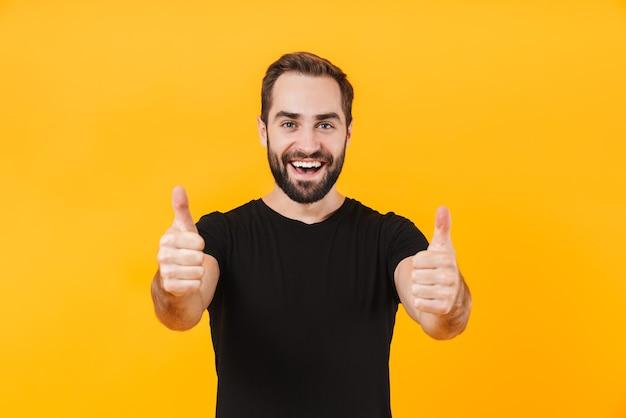 Довольный мужчина в простой черной футболке улыбается и жестикулирует большими пальцами, изолированными над желтой стеной