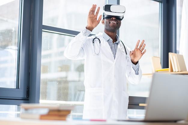 Довольный человек в униформе и поднимает руки во время тестирования виртуальной жизни