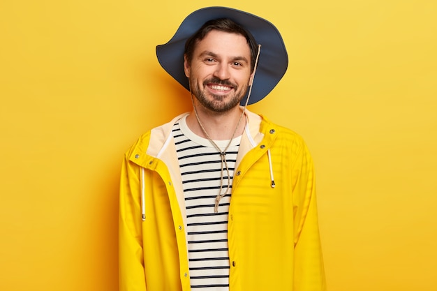 L'uomo soddisfatto indossa cappello, impermeabile giallo, trascorre il tempo libero attivamente, posa al chiuso, esprime buone emozioni, ha la barba incolta