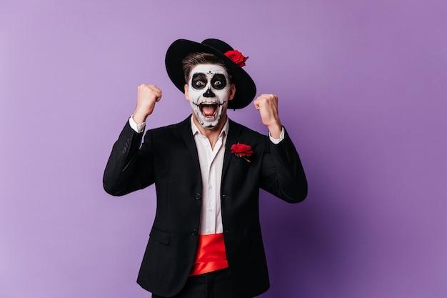 幸せを表現するメキシコの怖いメイクで喜んでいる男。死者の日を祝う至福の若い男性モデルのスタジオ写真。