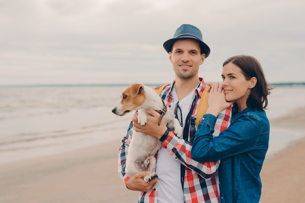 Pleased man and woman stand closely with favourite dog, look in distance, enjoy good day at seashore