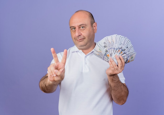 Довольный зрелый бизнесмен держит деньги и делает знак мира