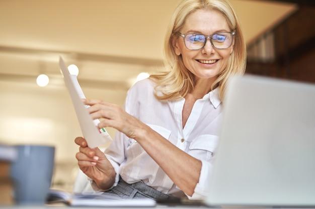 オンラインビデオ会議中に論文を議論するウェブカメラで笑っている成熟した実業家を喜ばせる